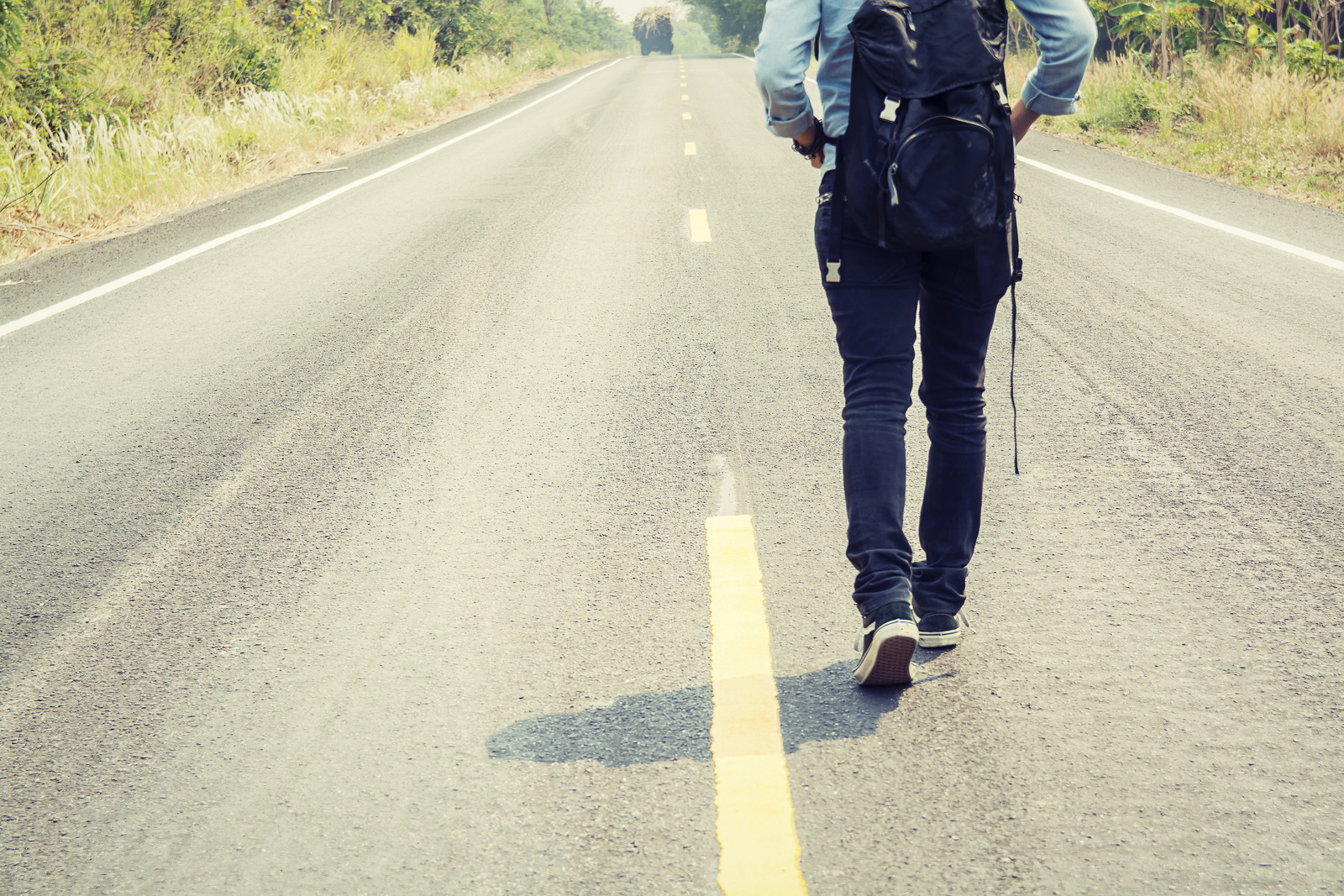 Rear view of a young woman hitchhiking carrying backpack walking